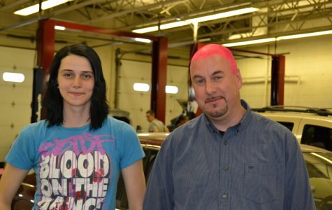 Alex Wolfe stands with her pink haired automotive teacher, Scott Freeman. The two made a bet that if Wolfe placed in the national automotive competition, he would paint his head pink.
