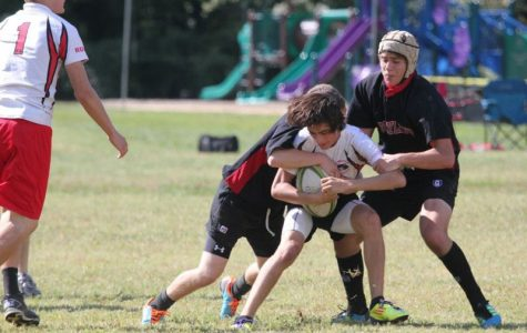 Junior Anthony Wright is tackled by rivals during a rugby match.