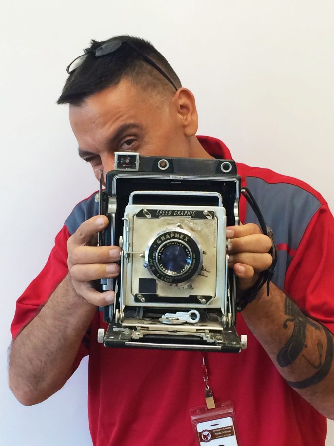 Reza Marvashti posing with a old time camera showing his love for photography.