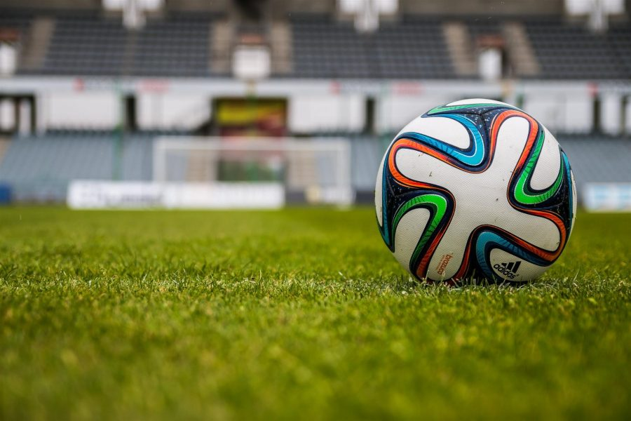A soccer ball on an empty field waiting for a change.