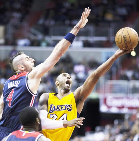 Kobe Byrant during a game shooting the ball hopeful to make a basket in the pursuit.