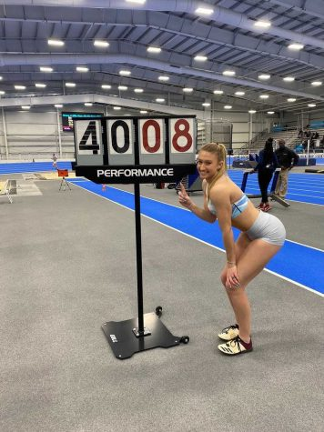 Senior Stephanie Robson posing next to her personal record sign at the Virginia Beach Sports Center.