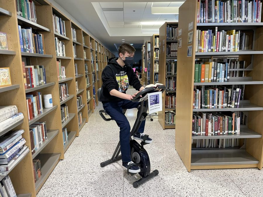 Spending time in the library, Freshman Nick Warren uses his advisory time to ride the new study bike.