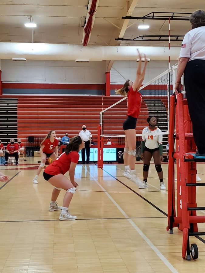 Junior Skyler Furr blocks an incoming hit during set four as her teammates cover her.