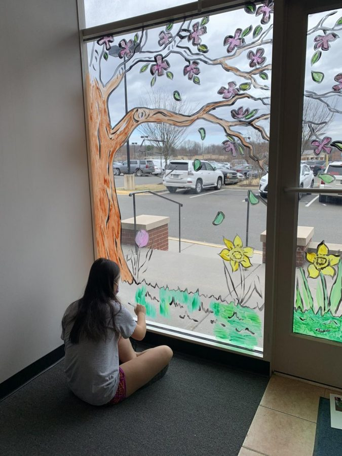 An FHS Student is painting the grass for the window display to show that