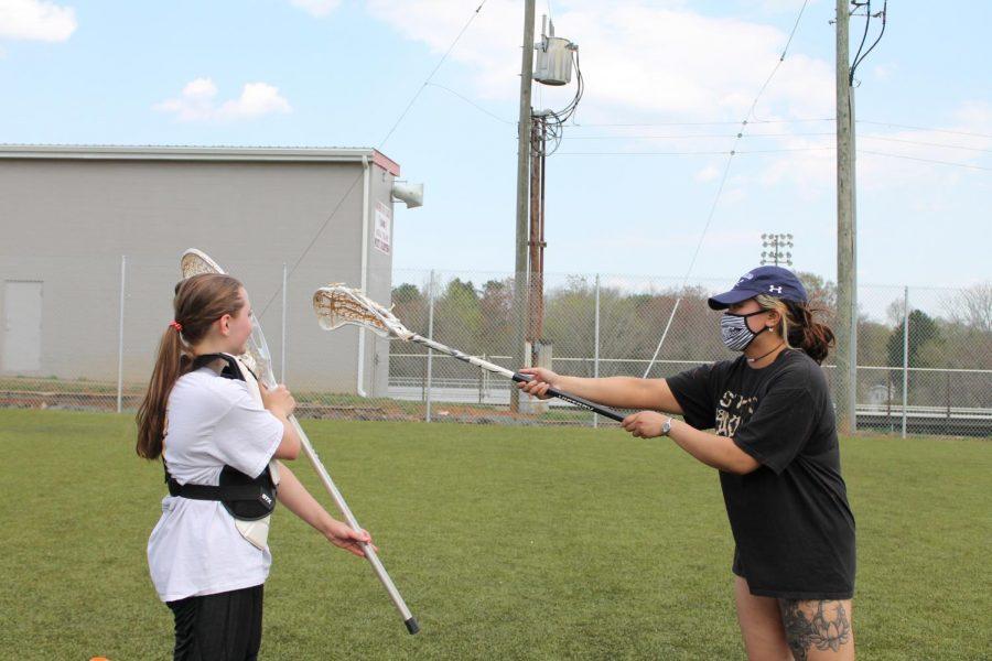 Assistant Coach A.J. Adan teaching the new goalie, Allyson Chesley.