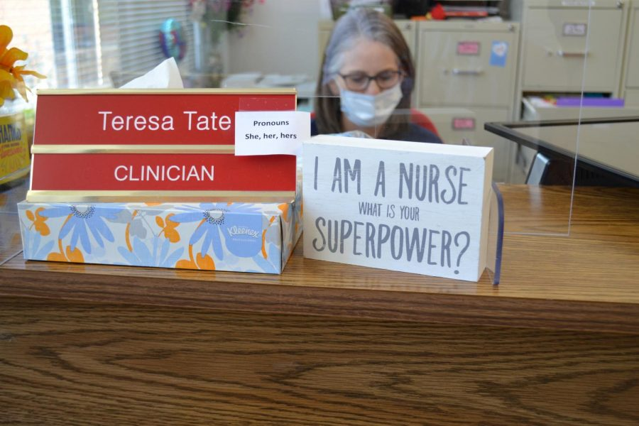 Nurse Teresa Tate works in the clinic reviewing and update paperwork and tending to student needs.